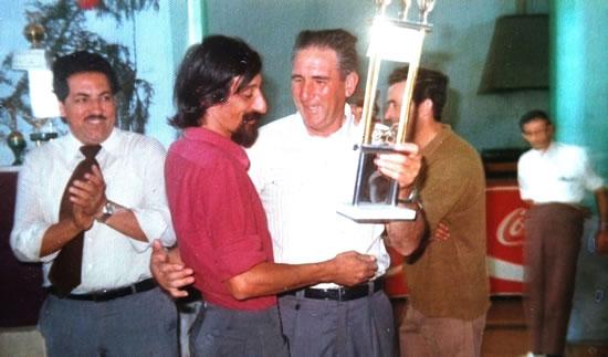 """Los socios del Club de Leones de Rocha, Andrés Solari y Elio López Arce, hacen entrega del trofeo ganado por el jinete rochense Carlos de los  Santos ( """"El Cuervo""""), en un Raid Hípico sobre 100 kilómetros."""